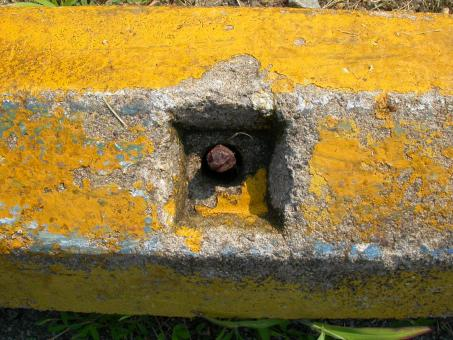 Free Stock Photo of Rusted bolt in yellow concrete wall