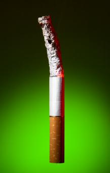 Free Stock Photo of Burned Cigarette on Green Background