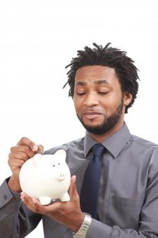 Free Stock Photo of Man putting money into a piggy bank