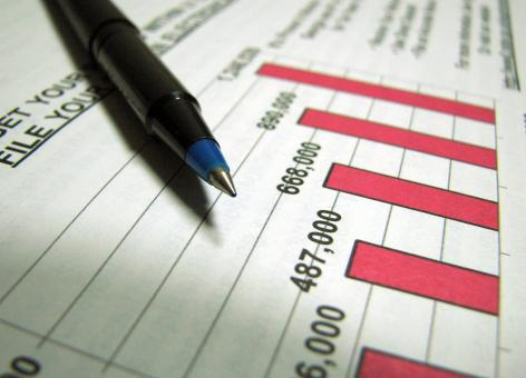 Free Stock Photo of Closeup of a tax income graph and pen