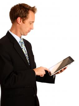 Free Stock Photo of A young businessman holding a tablet com