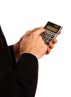 Free Stock Photo of Businessman in a suit using a calculator