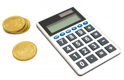Free Stock Photo of A calculator and a stack of gold coins