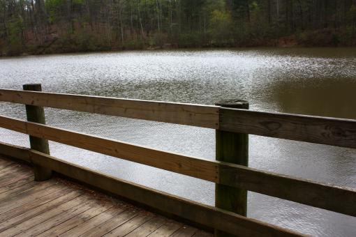 Free Stock Photo of A wooden fence by a lake