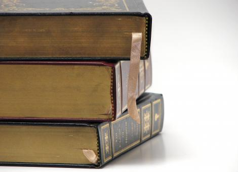 Free Stock Photo of Close-up of antique books on a white bac