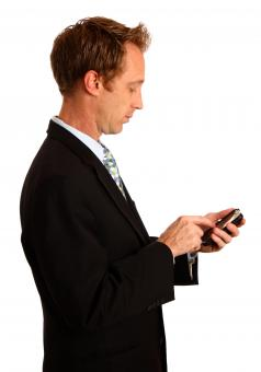 Free Stock Photo of A young businessman using a smart phone