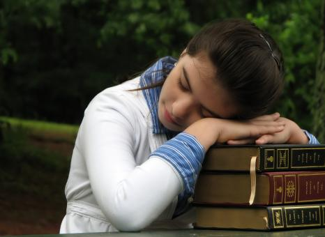 Free Stock Photo of Schoolgirl resting her head on books