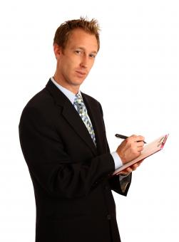 Free Stock Photo of A young businessman holding a clipboard