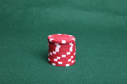 Free Stock Photo of Red poker chips on green felt.