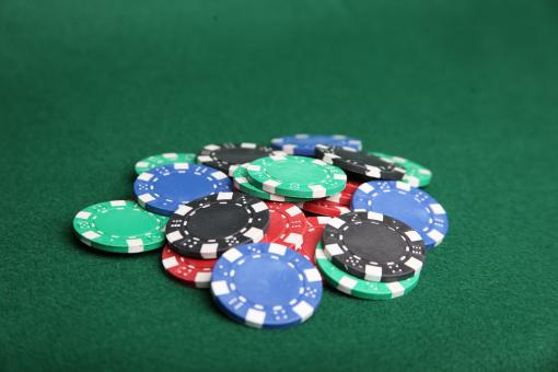 Free Stock Photo of Pile of poker chips on green felt.
