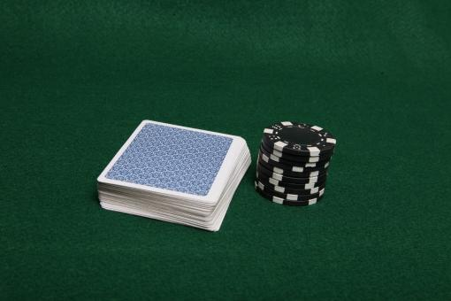 Free Stock Photo of Stack of black poker chips next to cards