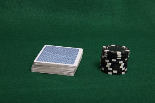 Free Stock Photo of Stack of black poker chips and deck of c