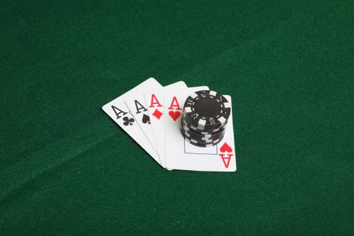 Free Stock Photo of Stack of black poker chips on four aces.