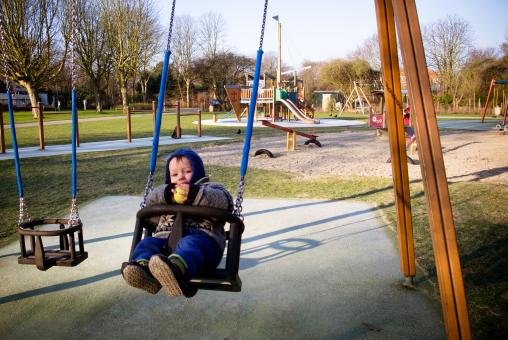 Free Stock Photo of Boy on swing in playground