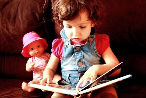Free Stock Photo of Child reading a book with doll