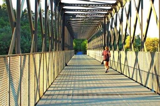 Free Stock Photo of Runner crossing a metal bridge