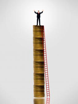 Free Stock Photo of Businessman on top of gold coin stack