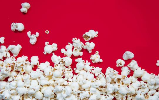 Free Stock Photo of Popcorn spilled on red background