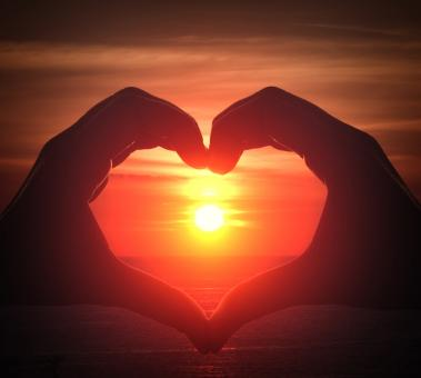 Free Stock Photo of Hand silhouette in heart shape with sunset in the middle