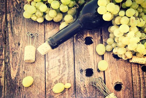 Free Stock Photo of Bottle of wine with grape and corks on wooden table - Rustic looks