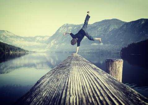 Free Stock Photo of Young boy handstanding on jetty