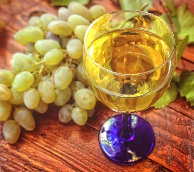 Free Stock Photo of Glass of white wine and a bunch of grapes in the background