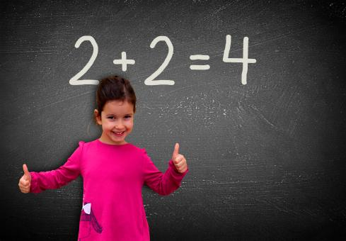 Free Stock Photo of Proud assertive little girl solving a sum on blackboard