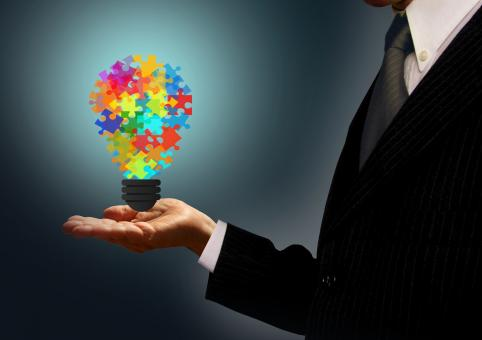 Free Stock Photo of Businessman holding a jigsaw lightbulb - Ideas and creativity concept