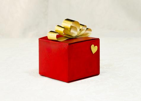 Free Stock Photo of Golden ribbon bow on a gift red box