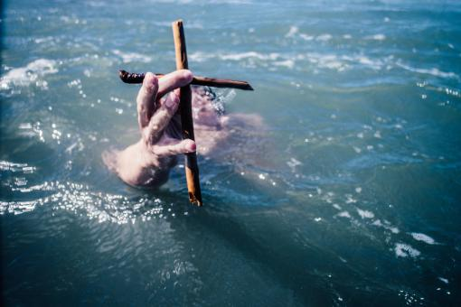 Free Stock Photo of Swimmer holding a cross