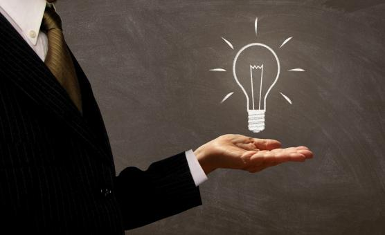 Free Stock Photo of Businessman Holding Light Bulb on Chalkboard