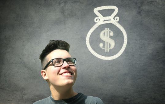 Free Stock Photo of Prize Winner - Young Man Smiling with Bag of Money