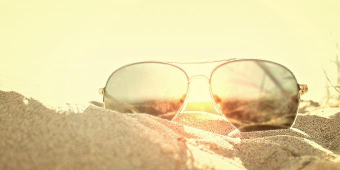 Free Stock Photo of Sunglasses on the Sand at Sunse