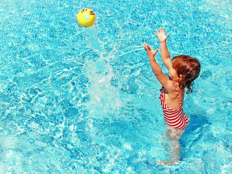 Free Stock Photo of Little Girl Playing with a Ball in the Swimming Pool