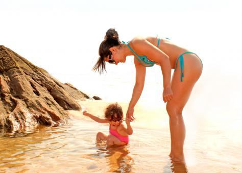 Free Stock Photo of Child bathing in a natural sea pool with the help of her mother