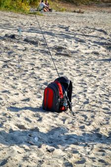 Free Stock Photo of Fisherman's bag with spinning rod lies on the sand