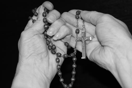 Free Stock Photo of Holding a Cross on String of Beads - Black & White