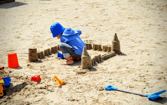 Free Stock Photo of A child plays with sand, sculpting a sand castle on a sandy beach