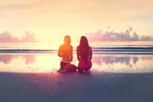 Free Stock Photo of Two Young Women Watching the Sunset Over the Ocean