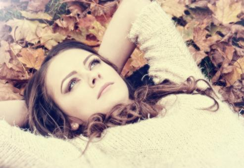 Free Stock Photo of Portrait of Dreamy Woman on Autumn Leaves