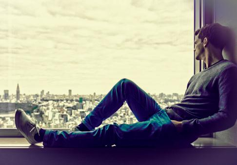 Free Stock Photo of Young Man Enjoying the City View at the Window - With Copyspace