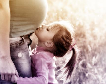 Free Stock Photo of Little Blonde Girl Kissing Pregnant Mother