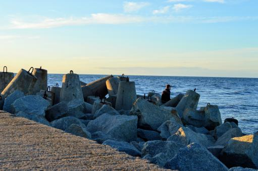 Free Stock Photo of  A man sits among tetrapod breakwater on the Baltic Sea