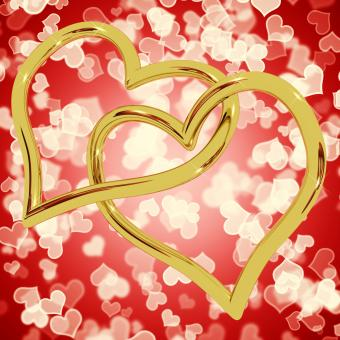 Free Stock Photo of Gold Heart Shaped Rings On Red Bokeh Representing Love And Romance