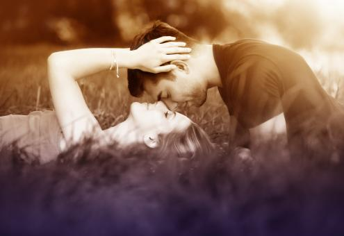 Free Stock Photo of Couple Kissing Laying on the Grass