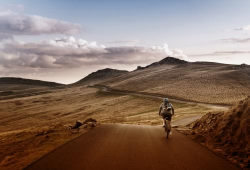 Free Stock Photo of  Lone Biker on the Road Through Mountains