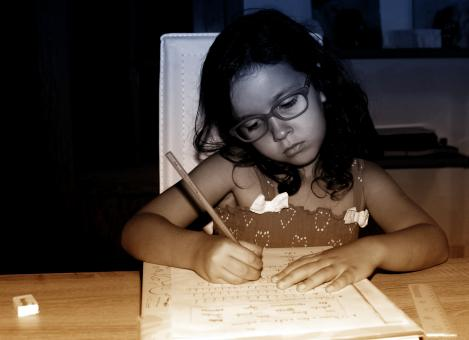 Free Stock Photo of Little Girl Focused On Doing Homework