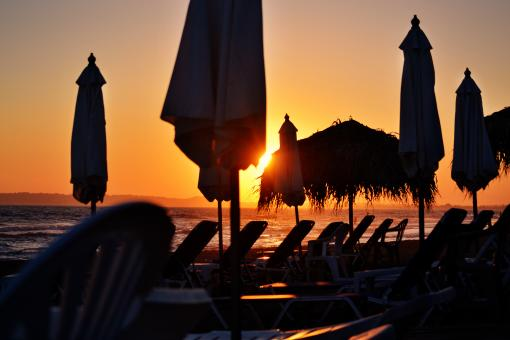 Free Stock Photo of Sunset Silhouettes of Sunbeds and Umbrellas by the Sea