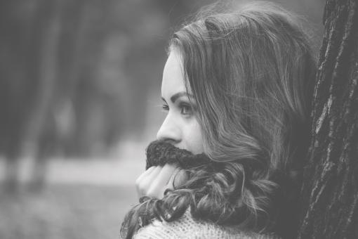 Free Stock Photo of Girl Looking Away with a Scarf on the Mouth and leaning by a Tree