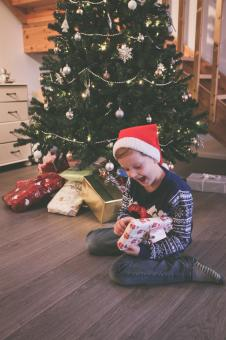 Free Stock Photo of Young Boy Opening Christmas Presents